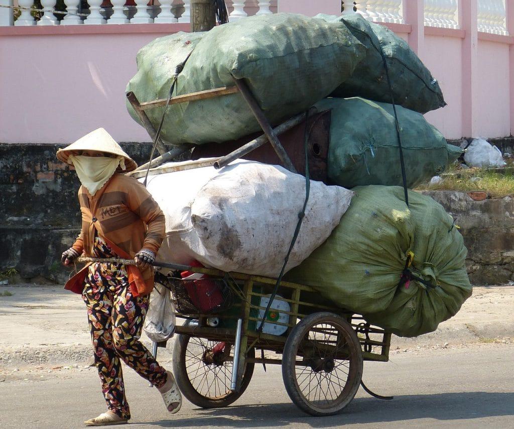 Вьетнамская женщина везёт мусор на тележке