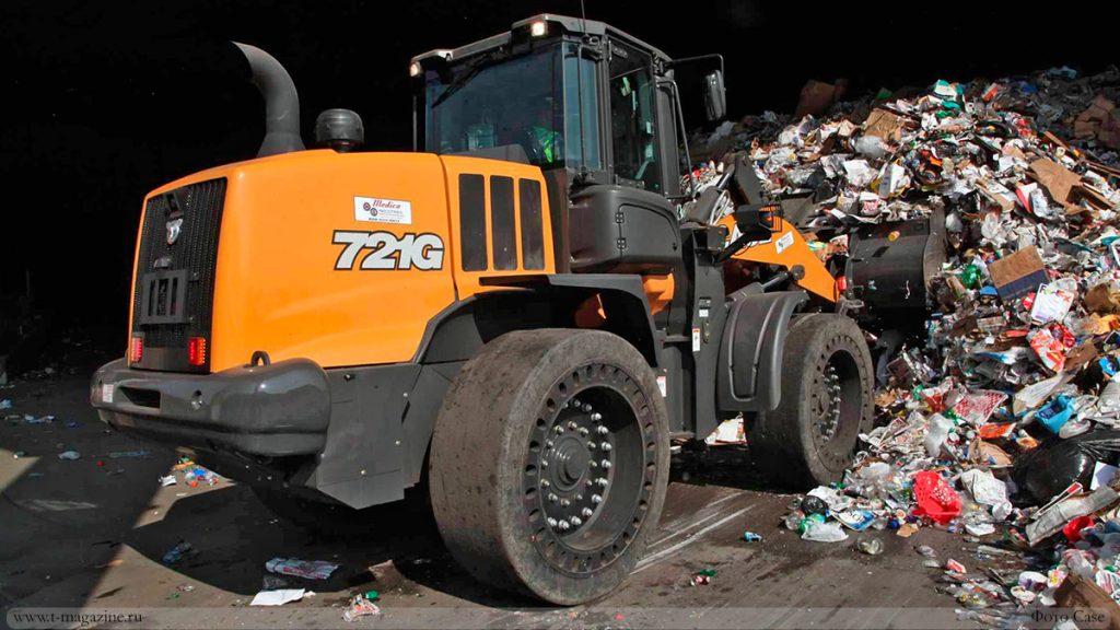 Погрузчик работает на мусороперерабатывающем заводе