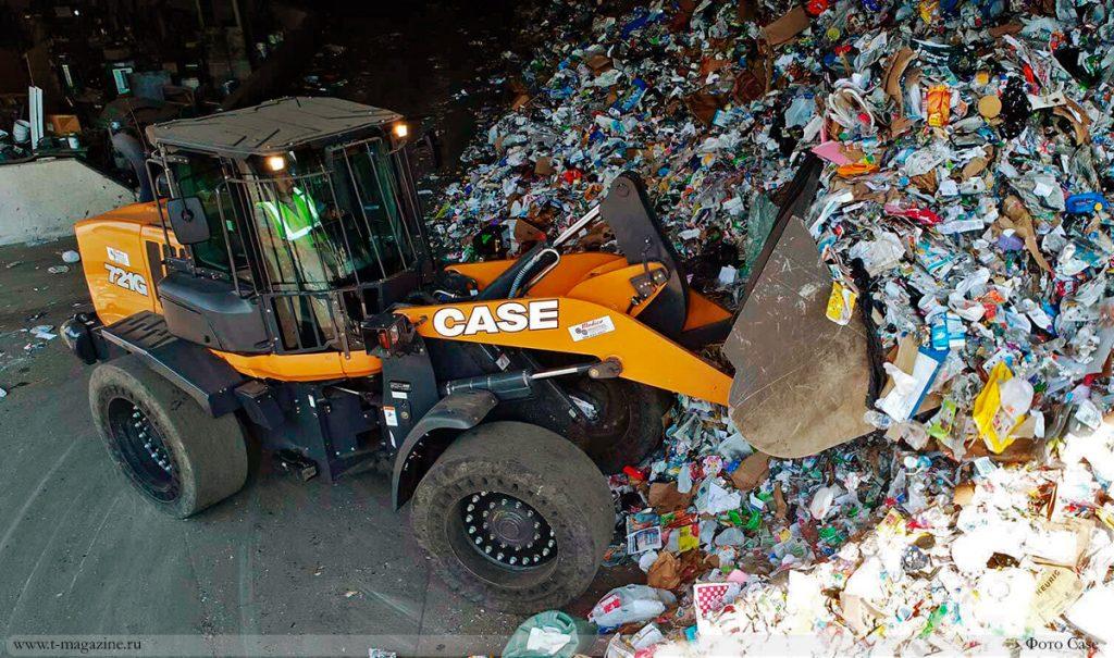 Фронтальный погрузчик загружает мусор из кучи