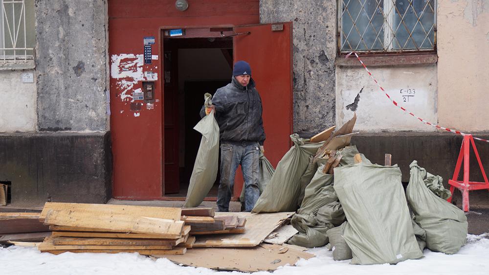 Человек выносит строительный мусор к подъезду