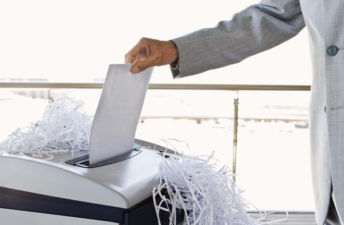 Человек уничтожает бумагу